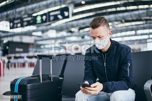 Man wearing face mask and waiting for flight at airport. Themes traveling during pandemic and personal protection.