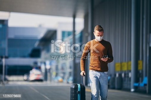 Man wearing face mask and walking to airport terminal. Themes traveling during pandemic and personal protection.