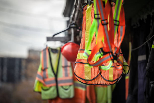 Personal protective equipments for sale on a shop: harness, reflective vests, yellow jackets, construction site helmets, as well as various other PPE devices Picture of PPE, or personal protective devices, for sale in a shop, haning. Yellow and Orange vests, harnesses and helmets are visible protective workwear stock pictures, royalty-free photos & images