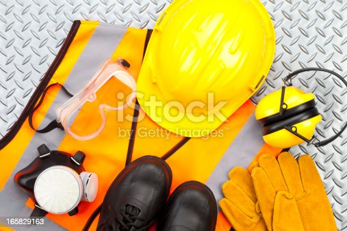 Industrial protective workwear shoot from above on diamond-plate background. Includes hard hat, safety glasses, earmuff, gloves, respiratory mask, steel toe shoes and safety vest. The predominant color is yellow, a color mostly used in safety items. Studio image taken with Canon EOS 5D Mk II