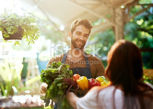 Shot of a man giving a customer a crate full of fresh produce at a farmer's market