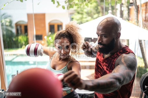 1069872470 istock photo Personal trainer and female boxer training 1181320277