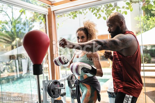 1069872470 istock photo Personal trainer and female boxer training 1181321025