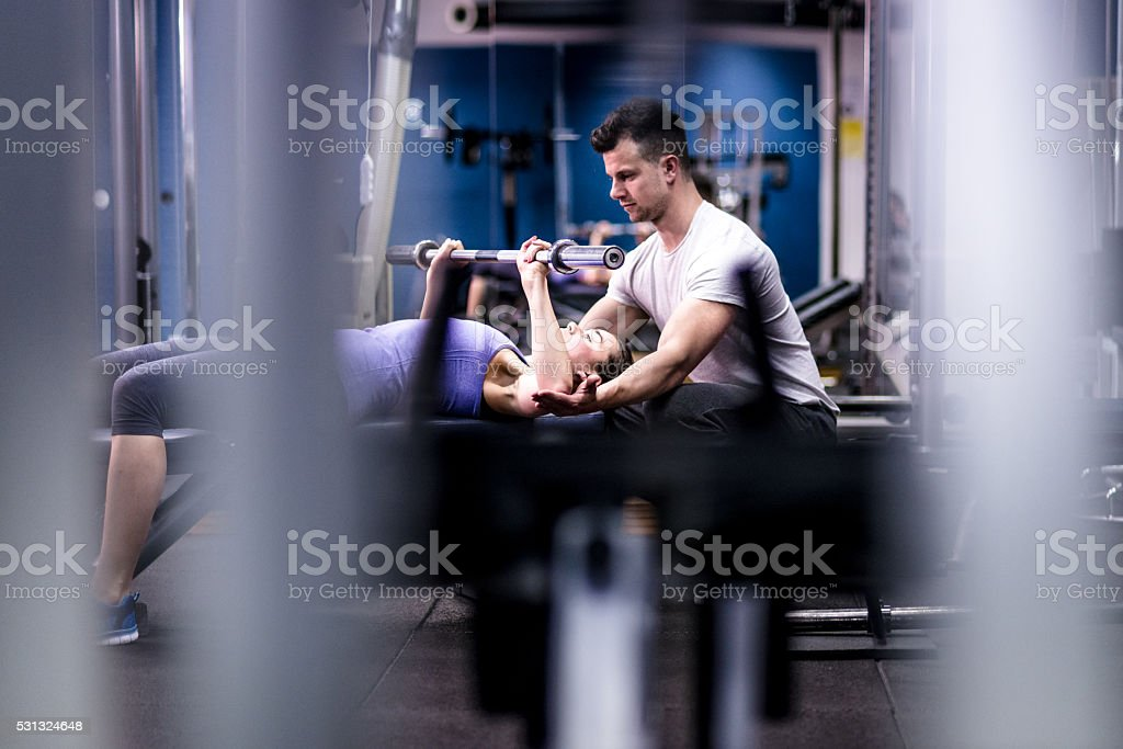 Personal trainer and woman at a gym stock photo