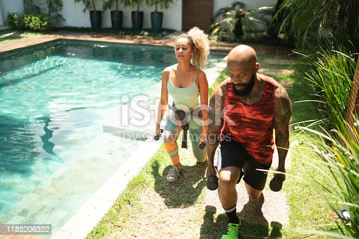 1069872470 istock photo Personal trainer and woman exercising in the yard 1183206322