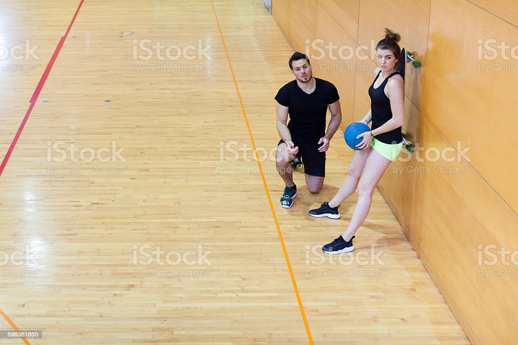 Personal Trainer Assist  Young Woman in Exercises Indoors royalty-free stock photo