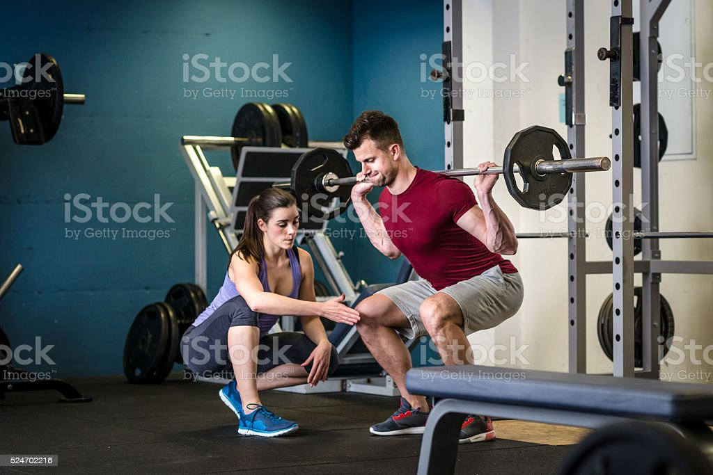 7e662b94ea9 Personal trainer assisting athletic client in weightlifting gym  royalty-free stock photo