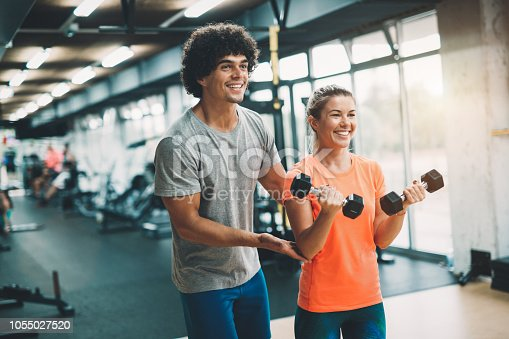 istock Personal trainer assisting beautiful woman lose weight 1055027520