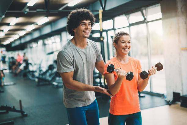 Personal trainer assisting beautiful woman lose weight stock photo