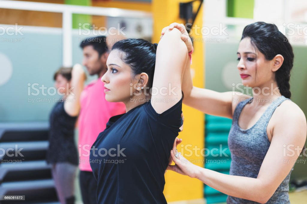 Personal trainer assisting her student in a yoga class practicing Gomukhasana position stock photo
