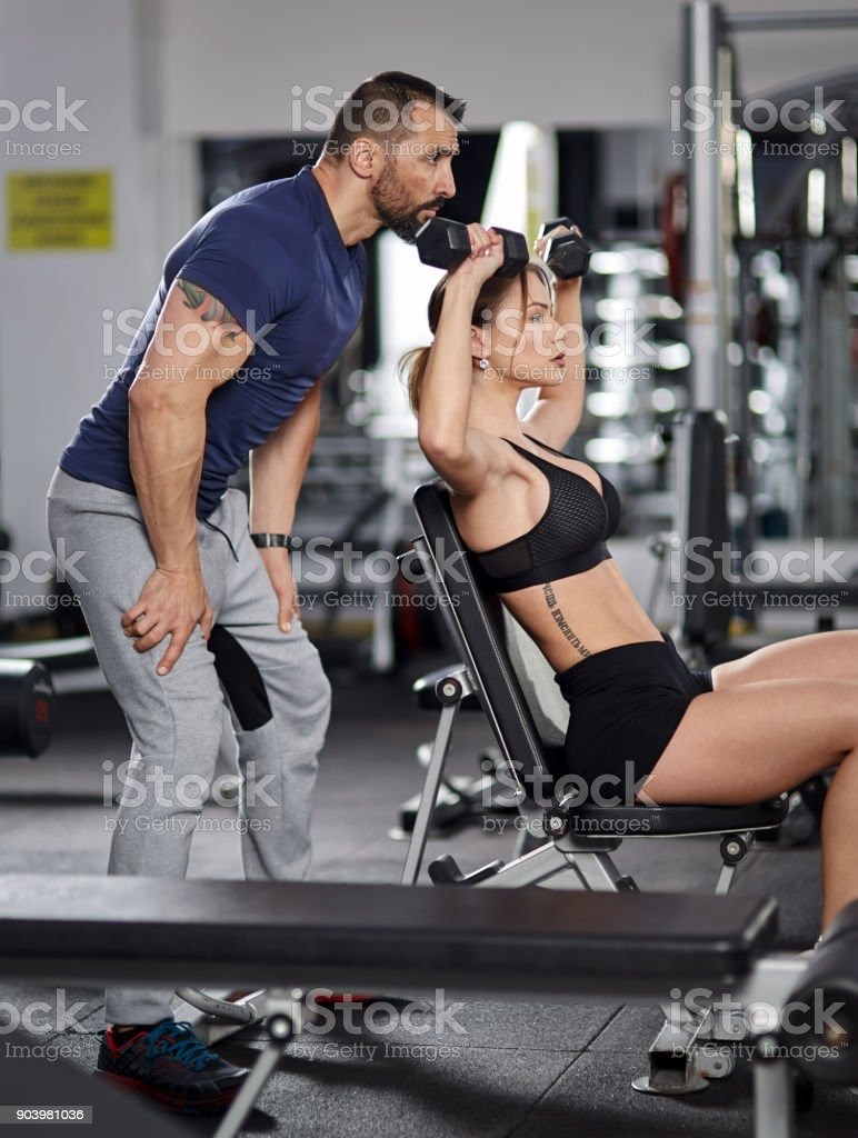 Personal trainer assisting young woman in the gym stock photo