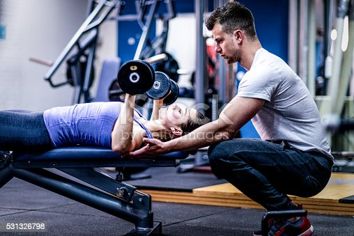 istock Personal trainer caring woman with her workout 531326798