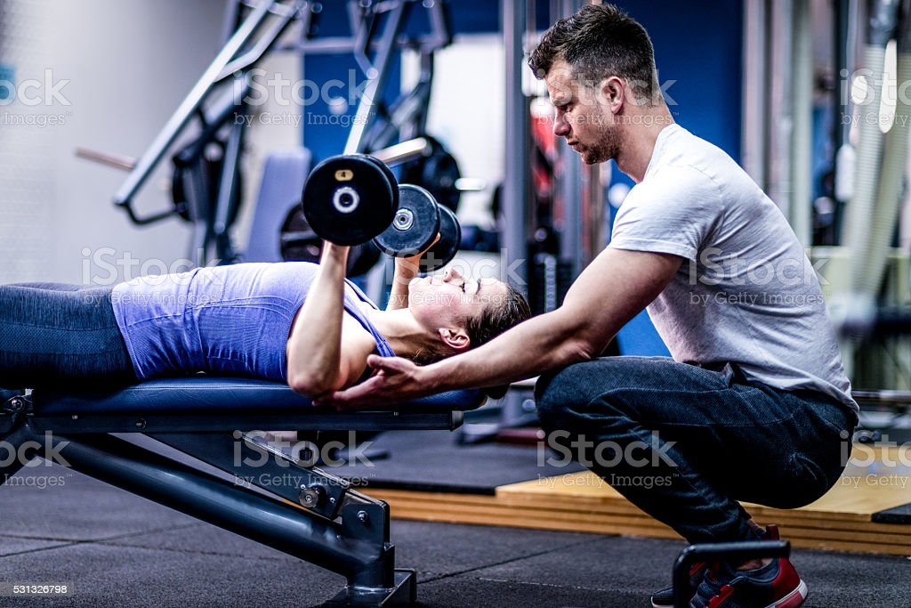 Personal trainer caring woman with her workout stock photo