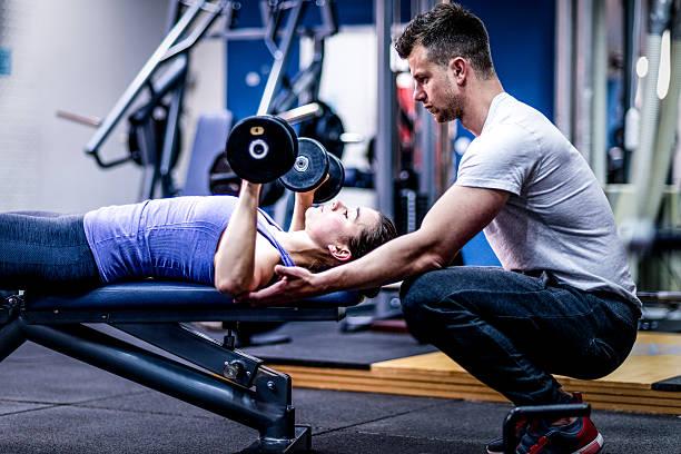 entrenador personal amable mujer con su rutina de ejercicios - entrenador personal fotografías e imágenes de stock