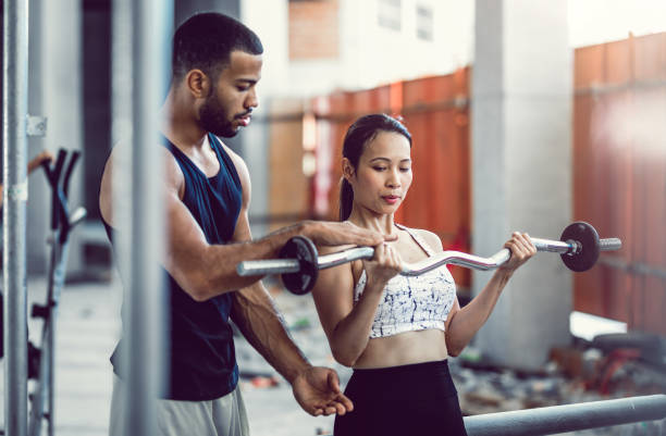 entrenador personal entrenamiento a un atleta femenina mientras levanta pesas - entrenador personal fotografías e imágenes de stock