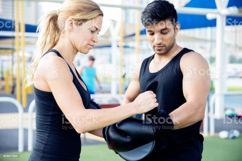 Personal trainer getting the trainee ready for boxing match stock photo