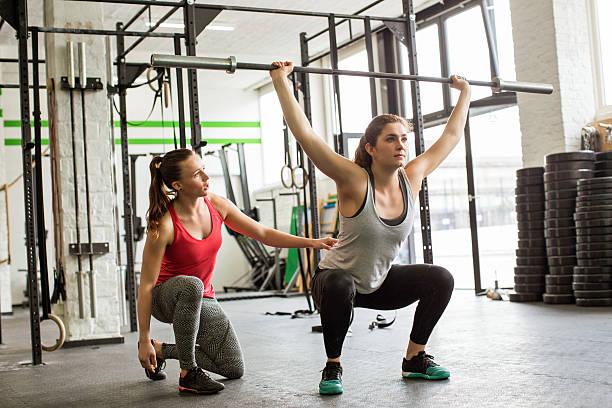 Entraîneur personnel conduite femme faire des squats avec haltères dans la salle de sport - Photo