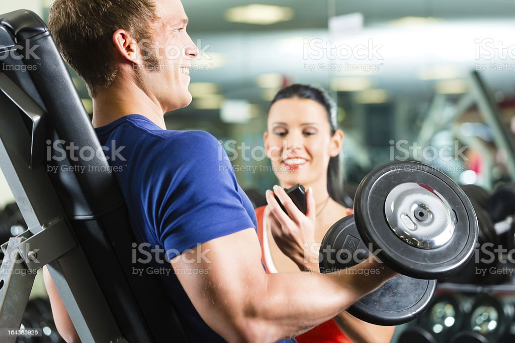 A personal trainer helping a man working out stock photo