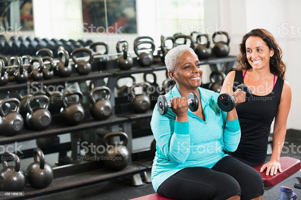 Personal trainer aiutando senior afro-americana in palestra - foto stock
