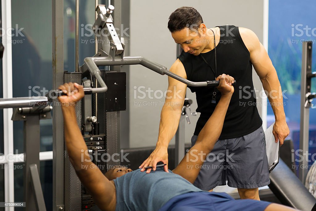 5546ed241db Personal Trainer Helping Client Lift Weights Stock Photo   More ...
