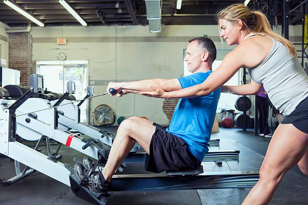 Entrenador Personal ayuda hombre con su rutina de ejercicios - foto de stock