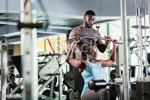 A mid adult man in his 30s working as a fitness instructor in a gym, helping a mature woman in her 50s strengthening her arms on exercise equipment. They are both African-American.