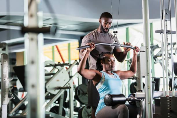entrenador personal ayudando a mujer madura en el gimnasio - entrenador personal fotografías e imágenes de stock
