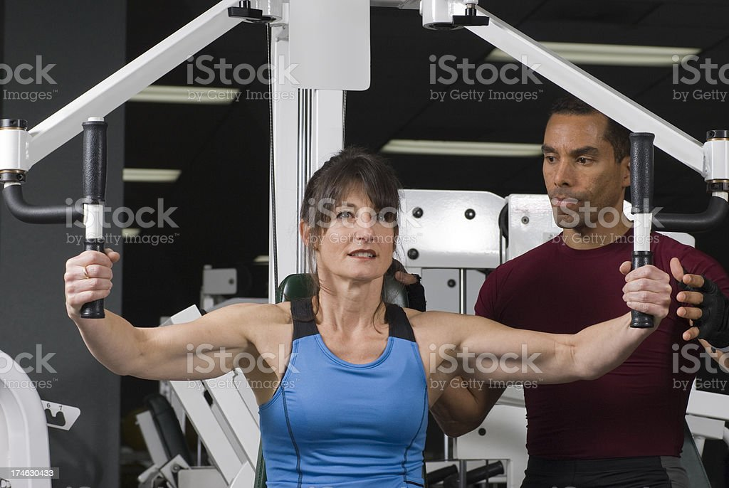 Personal Trainer Helping Woman on Flies Machine at Gym royalty-free stock photo