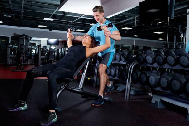 Persönlicher trainer helfen Frau arbeiten mit Hanteln – Foto