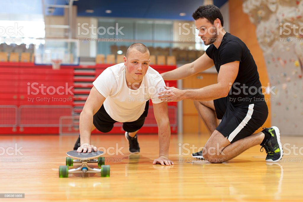 Personal Trainer Helping Workout Young Man royalty-free stock photo