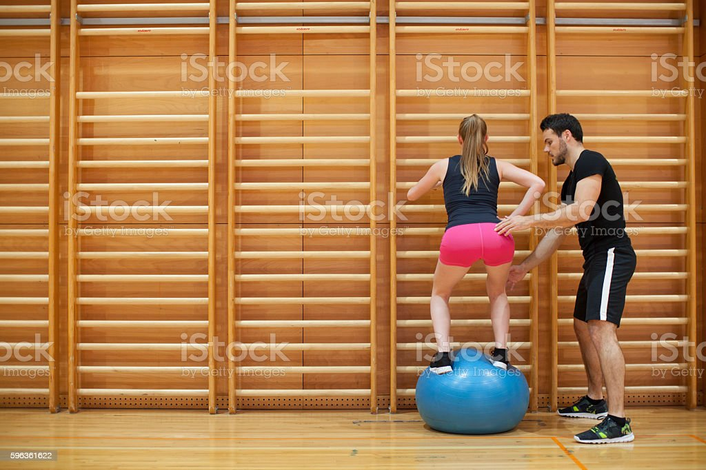 Personal Trainer Helping Workout Young Woman in Gym royalty-free stock photo