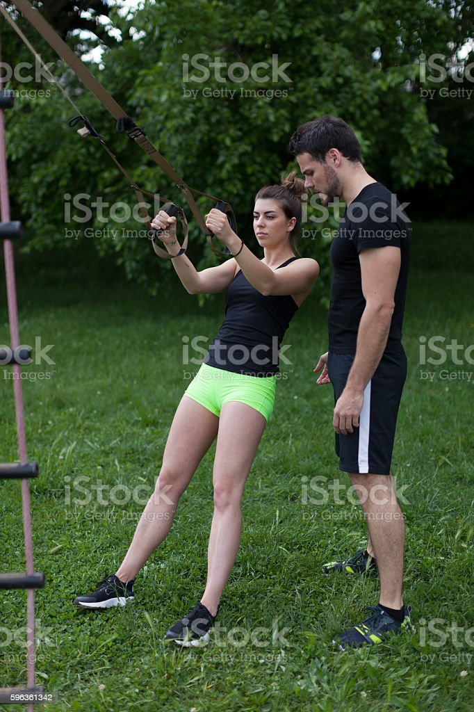 Personal Trainer Helping Workout Young Woman royalty-free stock photo