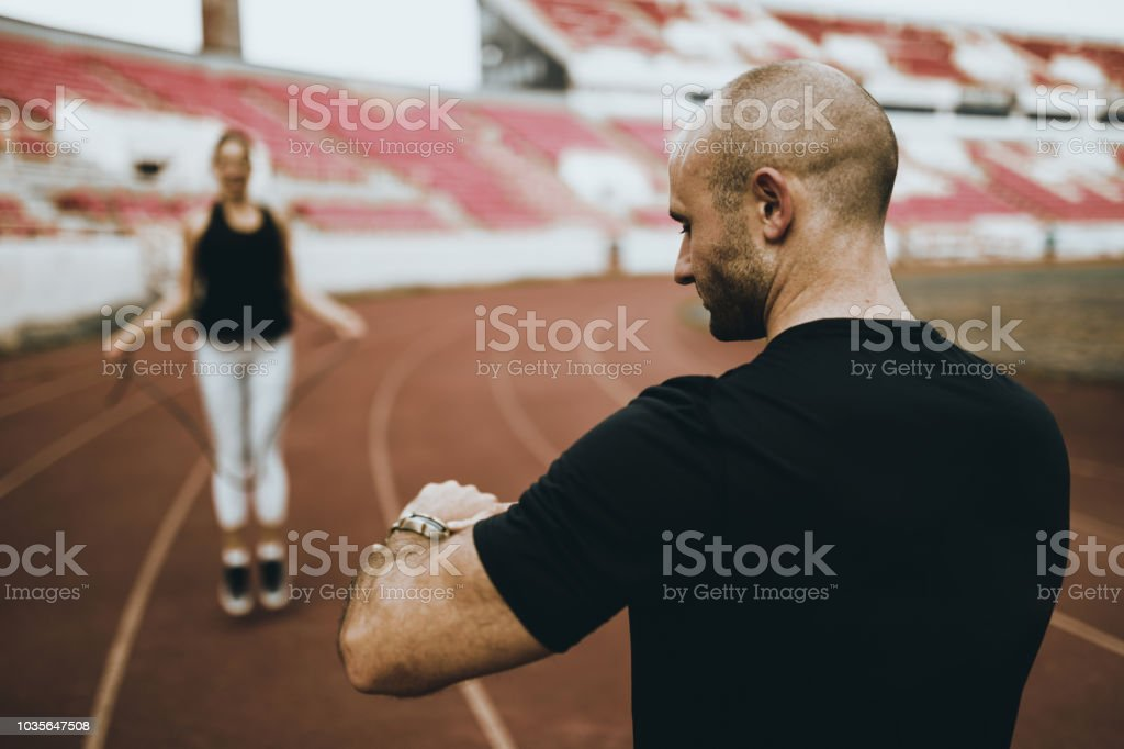 Personal trainer helping young woman with her sports training