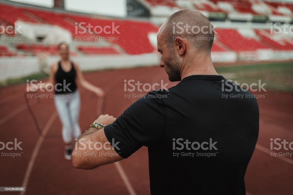 Personal trainer helping young woman with her sports training stock photo