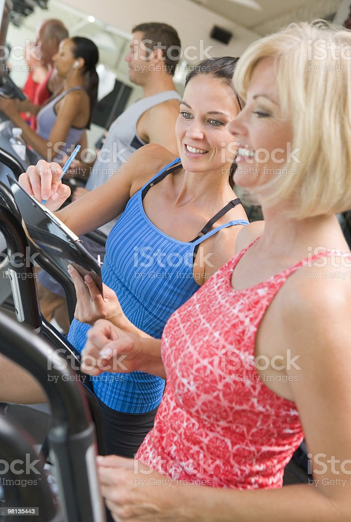 Personal Trainer Instructing Woman On Treadmill stock photo