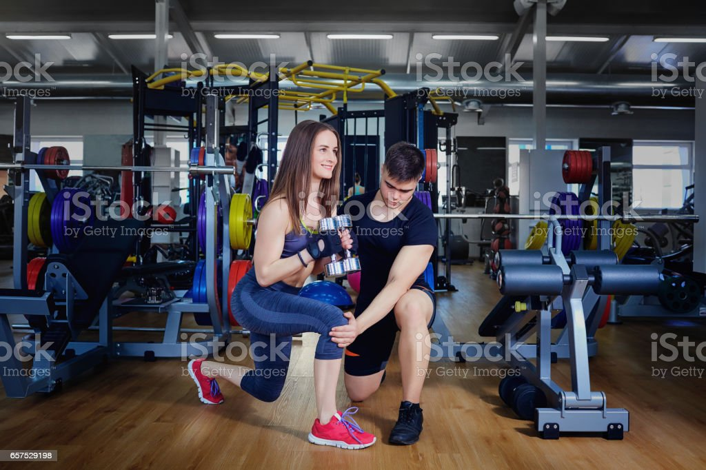 Personal trainer instructor helps to do exercises for sports girl in...