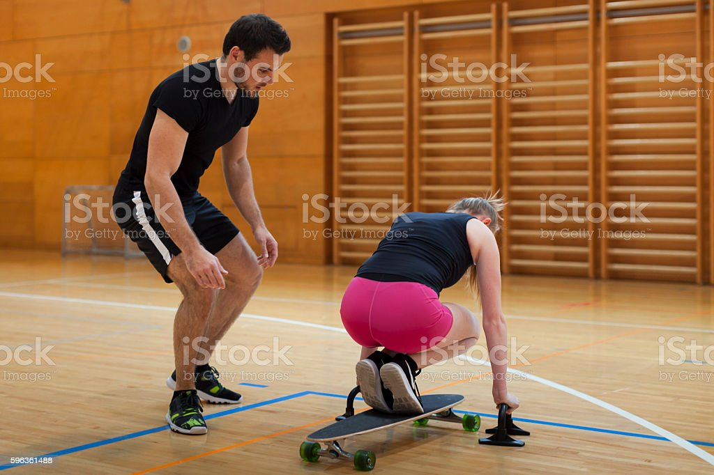 Personal Trainer Lead Young Woman Trough Exercise in Gym royalty-free stock photo