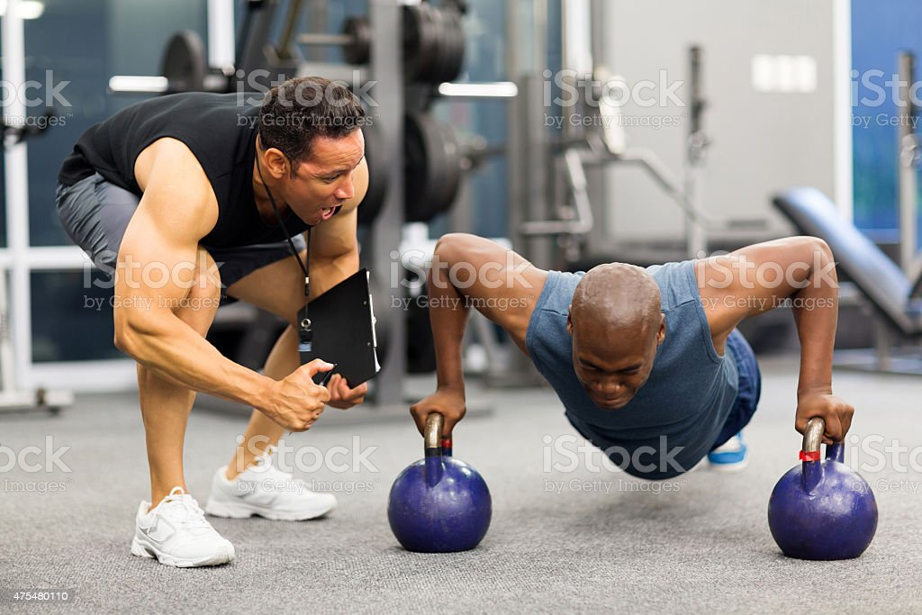 personal trainer motivates client doing push-ups stock photo