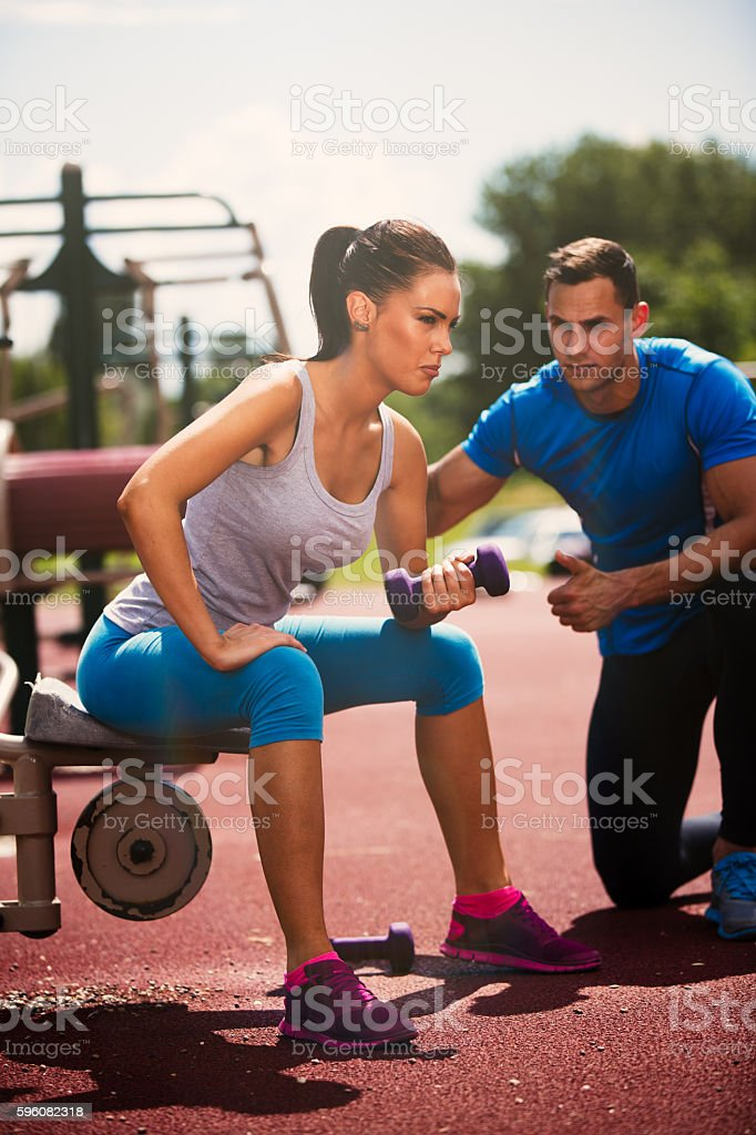 Personal trainer motivating young woman doing dumbbells exercise outdoors. royalty-free stock photo