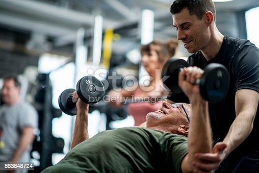 A senior man and a male trainer are indoors in a fitness center. They are wearing casual athletic clothing. The man is lifting weights with the guidance of the trainer.