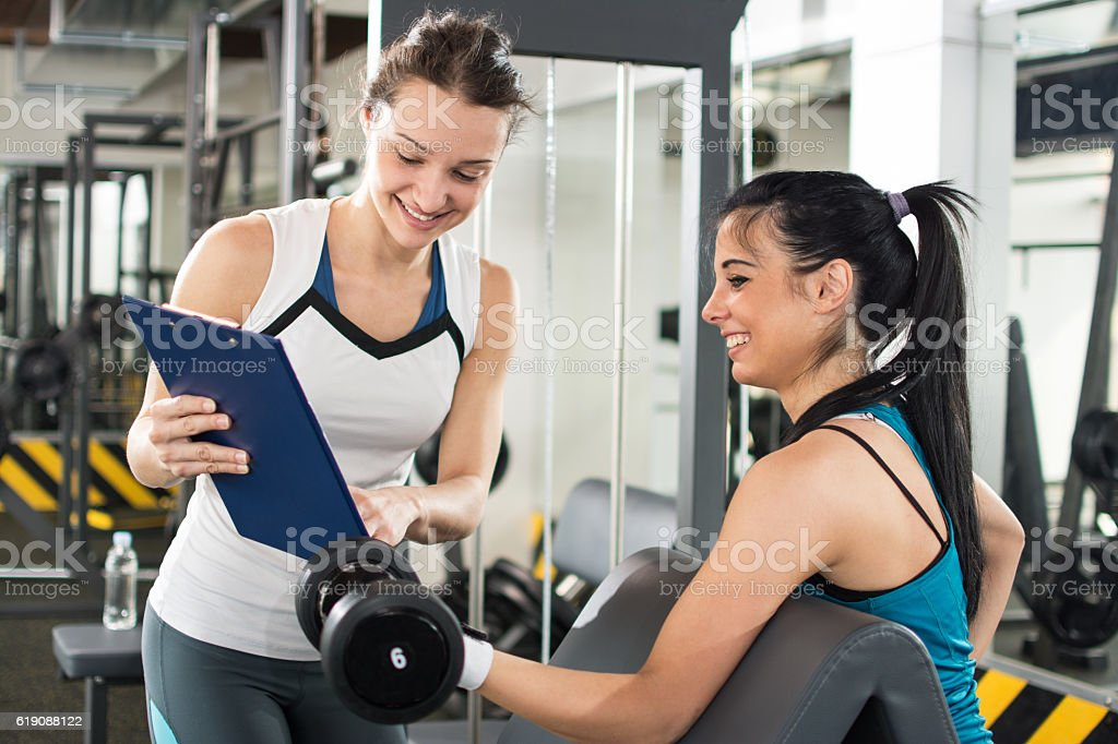 44224d9d76c Personal trainer showing exercise results to client in a gym. royalty-free  stock photo