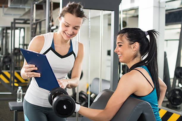 personal trainer showing exercise results to client in a gym. - trainingsplan frauen stock-fotos und bilder
