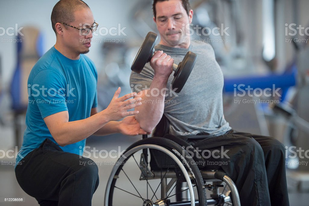 Personal Trainer Teaching a Man How to Lift Weights stock photo