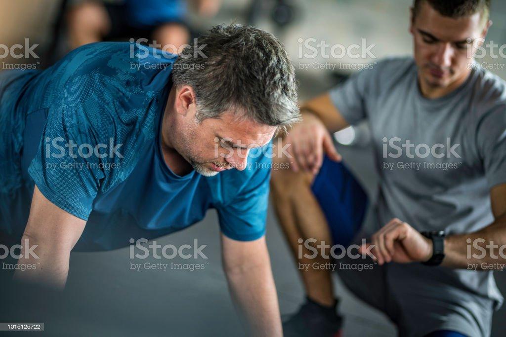 Personaltrainer timing seines Mandanten in eine Planke position – Foto