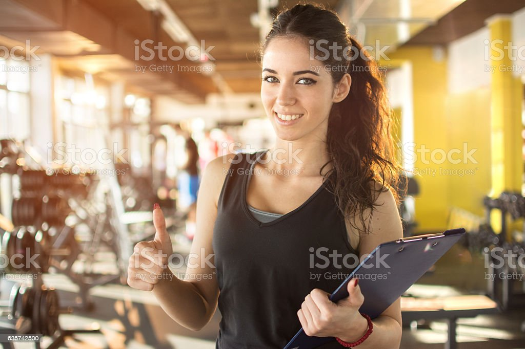 Personal trainer with clipboard showing thumb up in gym. stock photo