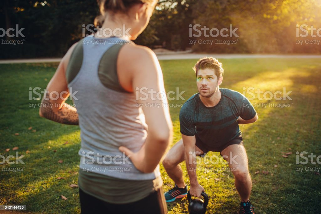 Personal trainer with man doing weight training in park stock photo