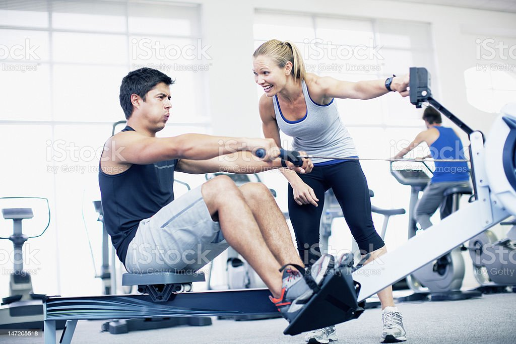 Personal trainer with man on rowing machine in gymnasium stock photo