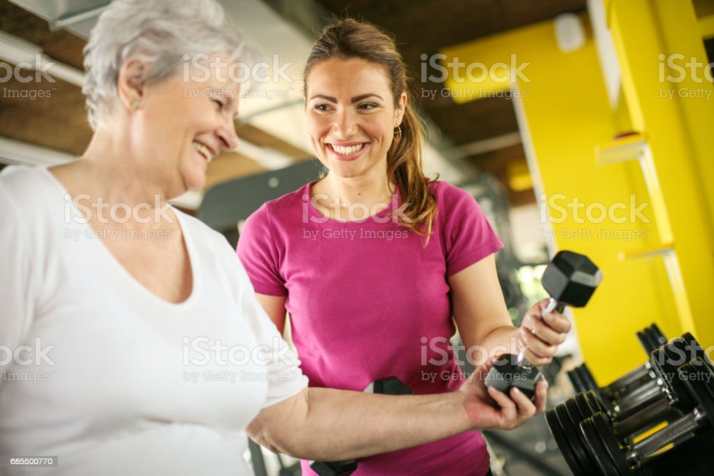 Personal trainer working exercise with senior woman in the gym. Woman picking weight. Workout in gym stock photo