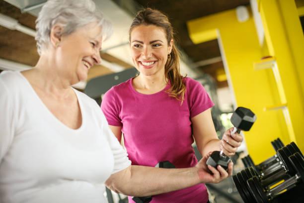 Entraîneur personnel occupant exercice femme senior dans le gymnase. Poids de femme de cueillette. Séance d'entraînement en gymnase - Photo