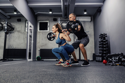 Personal training in the gym. A young woman and in sportswear and in good shape, she does barbell squats to strengthen the muscles of the whole body. The assistance of trainers in individual training